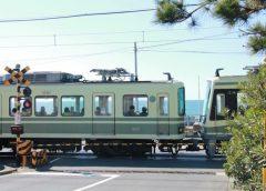 鎌倉高校前駅〜七里ケ浜駅間の踏切を走る江ノ島電鉄の車両