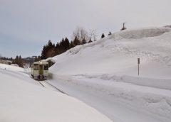 雪の積もるの飯山線内ケ巻駅に到着するJR東日本キハ110系気動車(イメージ) ©Katsumi