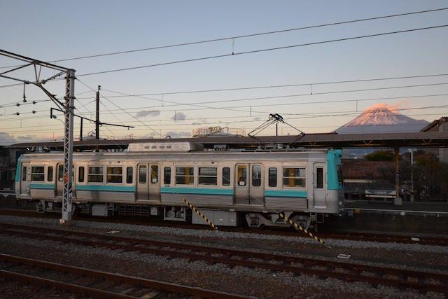 富士山を眺める吉原駅に停車中の岳南電車7000形電車(TOKYO STUDIO/Katsumi)