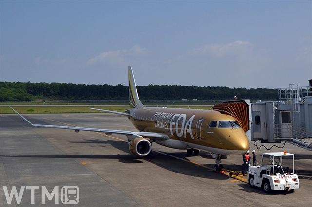 阿蘇くまもと空港に駐機中のゴールドカラーのFDA9号機/エンブラエルERJ-175(Katsumi/TOKYO STUDIO)